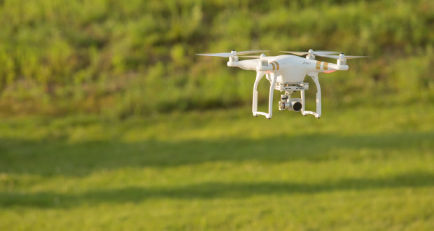 Remote control drone flying in mid air over a field